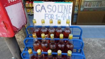 Garrafas de gasolina são vendidas pela estrada em toda a ilha